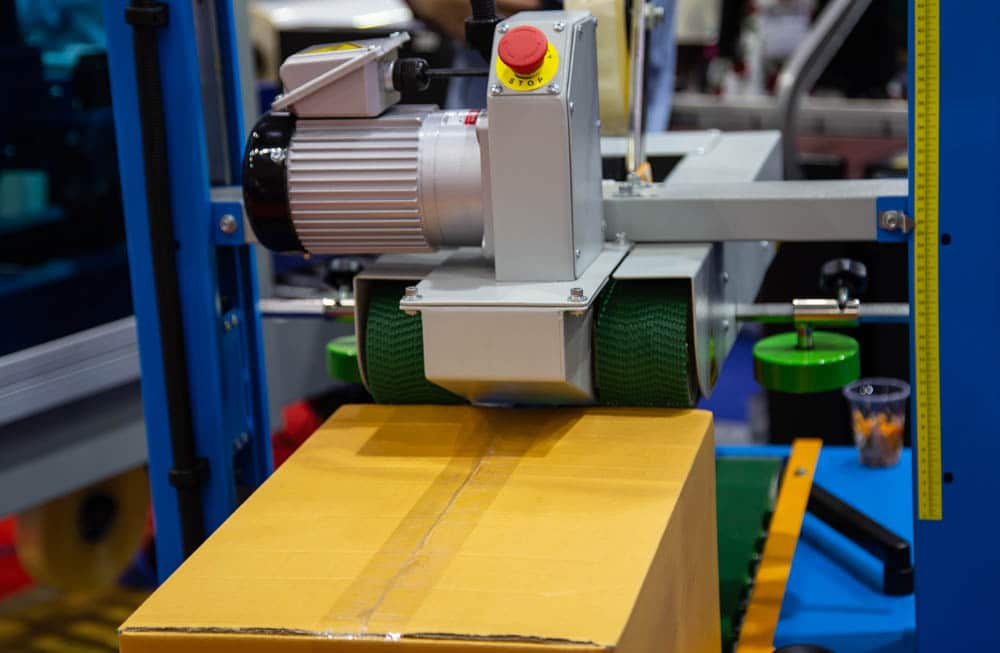 Automatic taper seals a package with masking tape