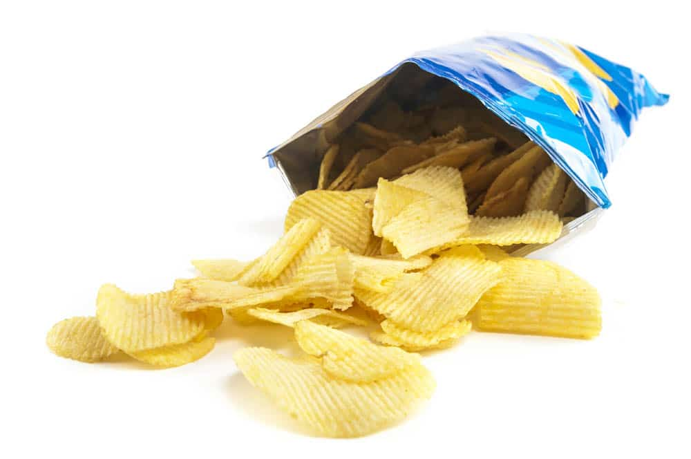 Potato chips spilling from a plastic chip bag